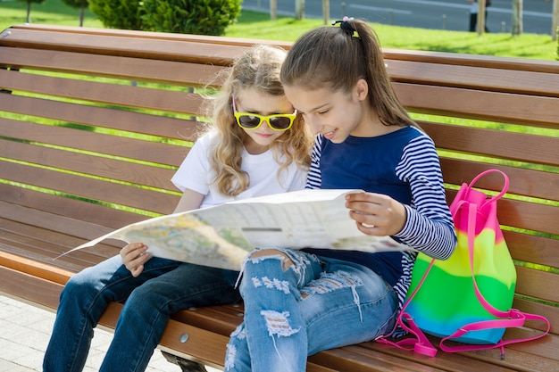 Children tourists with map of city on the bench