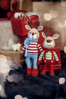 Children toys. two stylish amigurumi deers in striped sweaters, scarf and butterfly tie stands near christmas presents.