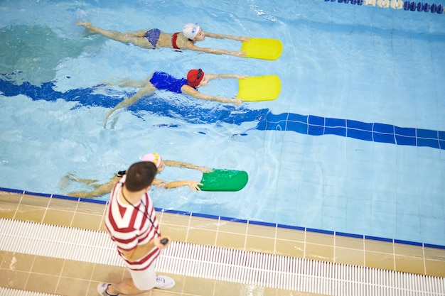 Children training with coach in pool