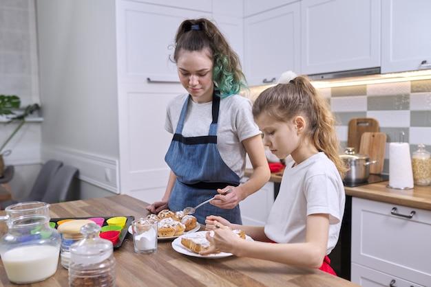 아이들은 집 부엌에서 머핀을 준비하는 두 여자 자매입니다. 갓 구운 수제 케이크에 백설탕 가루를 뿌리는 아이들
