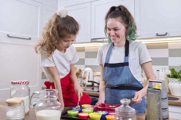 家庭の台所でマフィンを準備している子供2人の女の子の姉妹。キッチンで一緒に若いものと古い10代の少女。フレンドリーな家族、楽しんで、自家製のベーキング、家庭生活