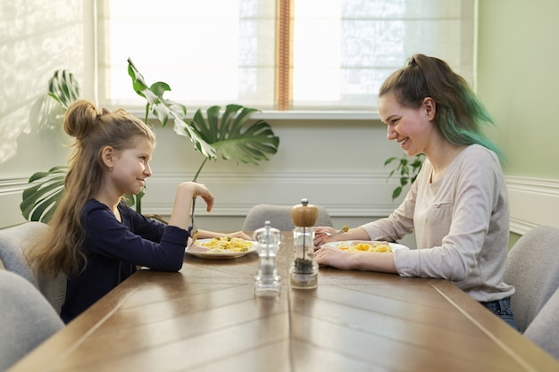 Children two girls sisters teenager and younger eat lunch sitting at table in home kitchen, homemade food, family communication