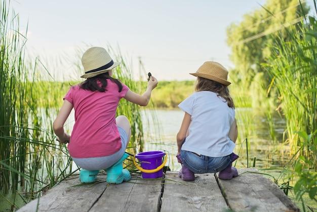 갈대 나무 부두에 있는 호수에서 물을 가지고 노는 두 여자 아이. 조류와 물 달팽이의 양동이 따기 막대기를 가진 아이들. 자연, 레저, 우정, 여름 휴가 개념