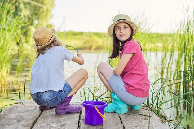 葦の木造桟橋の湖で一緒に水遊びをしている2人の女の子の子供たち。藻類とカタツムリのバケツ狩り棒を持つ子供たち。自然、レジャー、友情、夏休みのコンセプト