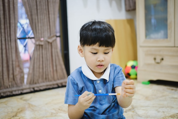 Children use watercolor brushes to draw on their arms to create imagination and enhance their learning skills.