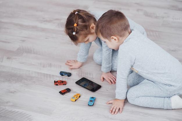 自宅でデジタルガジェットを使用している子供たち。パジャマ姿の兄妹は、テクノロジータブレットで漫画を見たりゲームをしたりします。