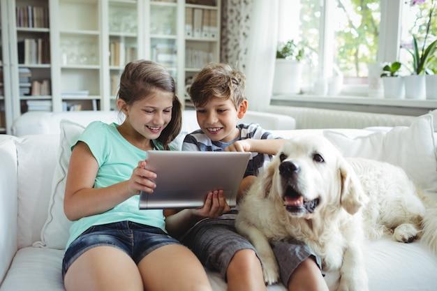 Дети с помощью цифрового планшета, сидя на диване