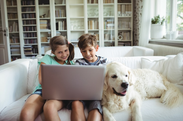 Дети с помощью ноутбука, сидя на диване
