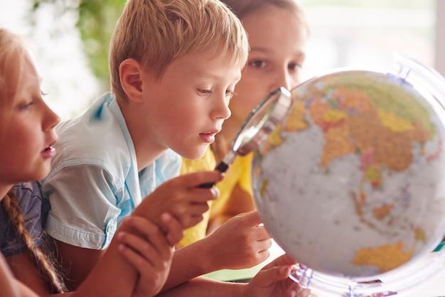 地理学で虫眼鏡を使用している子供たち