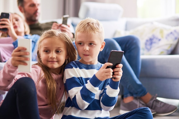 Bambini che usano il cellulare in soggiorno