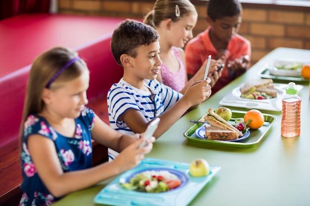 Children using smartphones during lunch