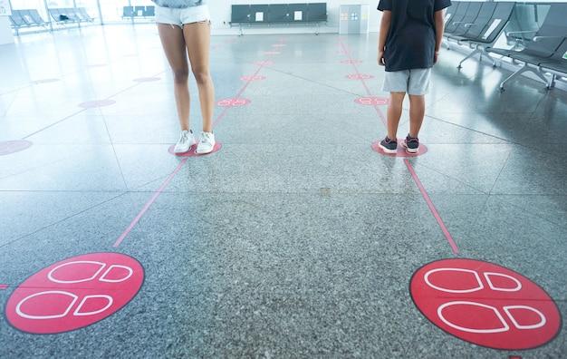 사회적 거리를 유지하기 위해 지상 표시에서 기다리는 아이들. covid 19를 피하기위한 사회적 거리.