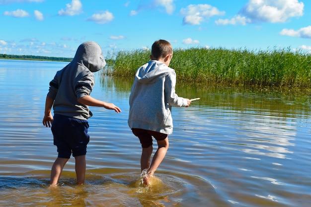 子供たちは水の中を歩きます。子供たちは手で魚を捕まえます。