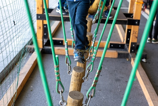 Children walking on trunks suspended by ropes in an adventure park.