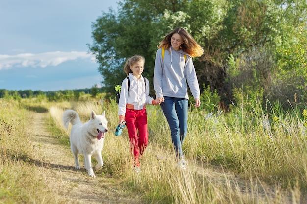 Дети гуляют с белой собакой на лугу в осенний день