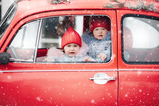Children in warm clothes bask in a red car during snowfall
