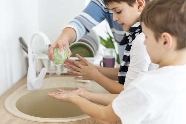 Children washing their hands with the help of their mother