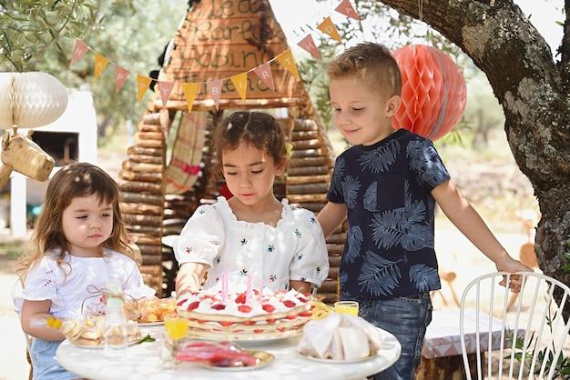 食べようとしているバースデーケーキを見ている子供たち