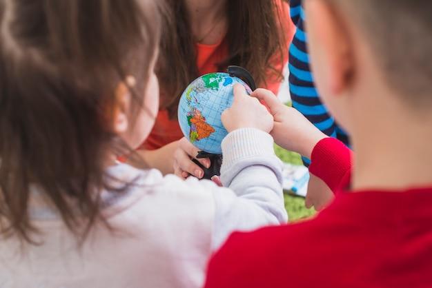 Bambini che guardano e toccano il globo