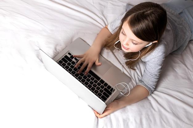 ハイテクの機会を利用して互いにコミュニケーションをとる子供たち 自宅での女子高生 子供たちのオンライン教育と遠隔学習 検疫中のホームスクーリング
