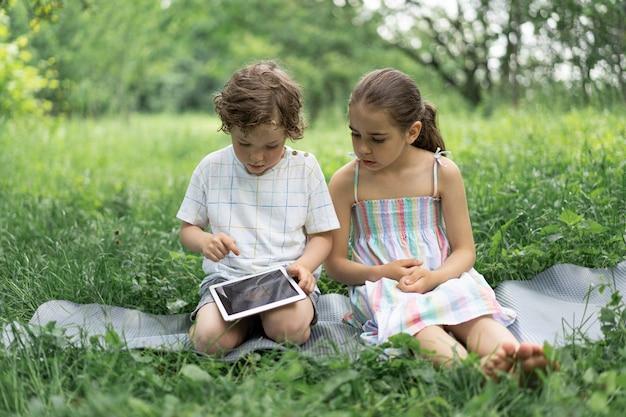 屋外でタブレットを持っている子供たち子供たちはタブレット技術の概念でゲームをします
