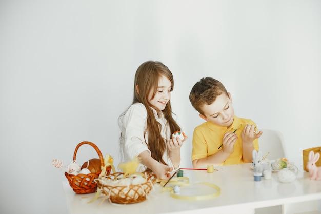 バニーの耳を持つ子供たち。塗装されたイースターエッグ。絵の具とブラシを持った子供たち。
