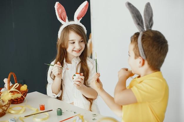 토끼 귀를 가진 아이들. 그린 부활절 달걀. 페인트와 붓을 가진 아이들.