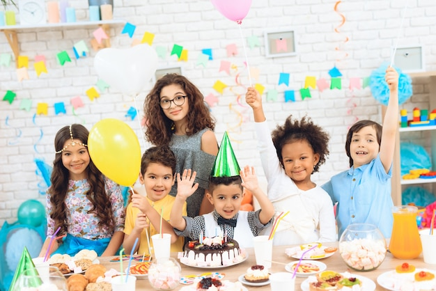 Children with color balloons sit behind festive table.