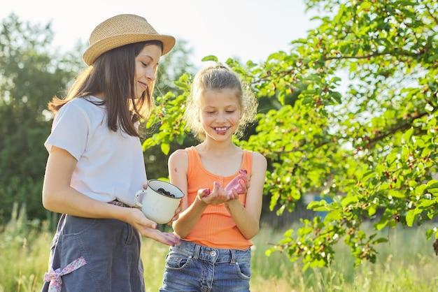 머그에 딸기를 든 아이들, 여름 정원에 있는 뽕나무. 비타민이 풍부한 맛있고 달콤한 천연 베리
