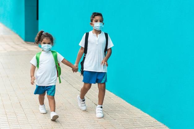 コロナウイルスの発生中に学校に戻るフェイスマスクを持つ子供たち-子供の顔に焦点を当てる