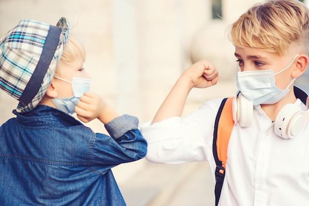 学校に戻るフェイスマスクを持つ子供たち。新しい挨拶スタイル。子供たちは屋外で肘をぶつけます。社会的距離。コロナウイルスパンデミック時の教育。