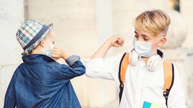 学校に戻るフェイスマスクを持つ子供たち。