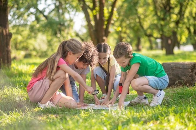 Children with map and magnifying glass on lawn