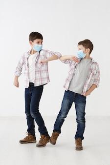 Bambini con maschere mediche che dimostrano saluti senza contatto