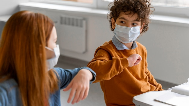 クラスで肘の敬礼をしている医療用マスクを持った子供たち