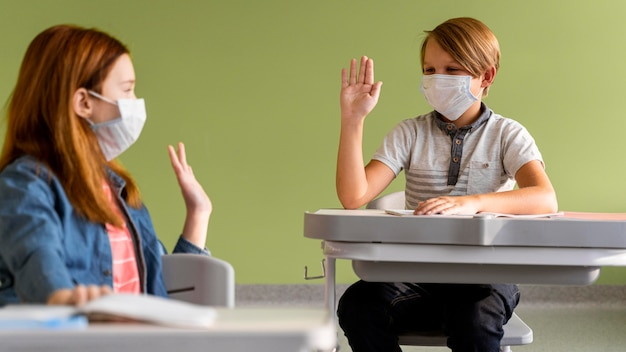 Children with medical masks high-fiving each other from distance
