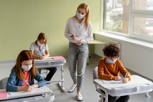 教師と一緒に学校で学ぶ医療マスクを持つ子供たち