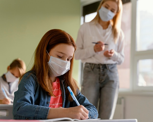 Bambini con maschere mediche che imparano a scuola con insegnante femminile