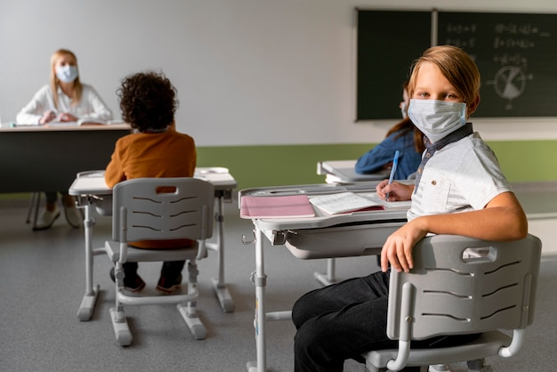 Children with medical masks learning in school with female teacher