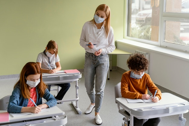 Children with medical masks learning in school with teacher