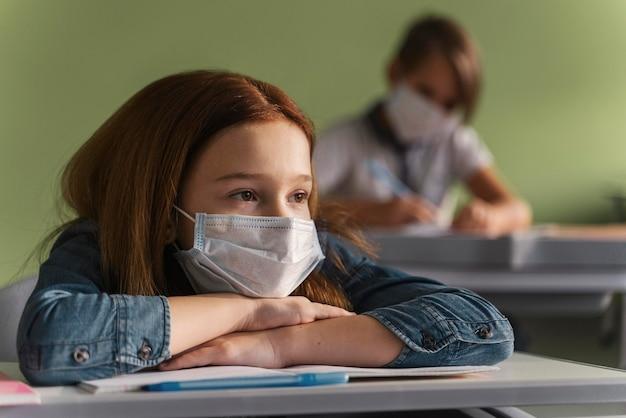 クラスで先生の話を聞いている医療用マスクを持った子供たち