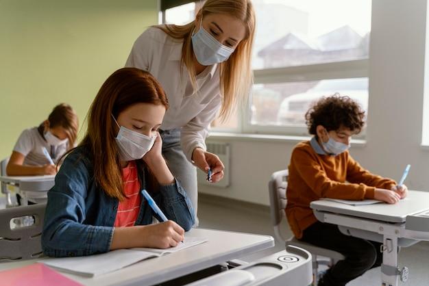 教師と一緒に学校で勉強している医療用マスクを持つ子供たち