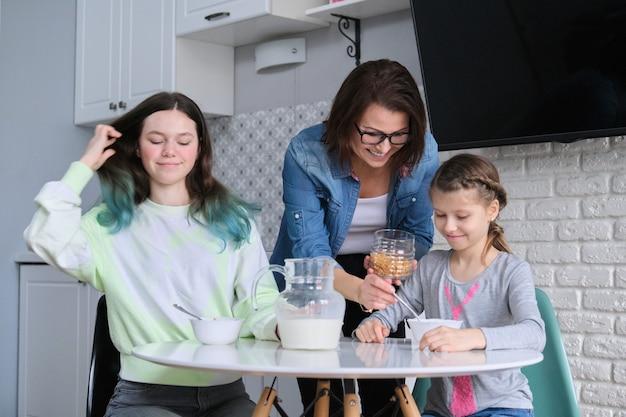 집에서 부엌에서 식사하는 어머니를 둔 아이들, 콘플레이크와 우유 접시를 들고 식탁에 앉아 있는 두 소녀. 가족, 식사, 의사 소통, 건강 개념.