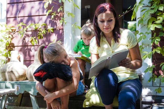 ポーチで母親が読んでいる子供たち