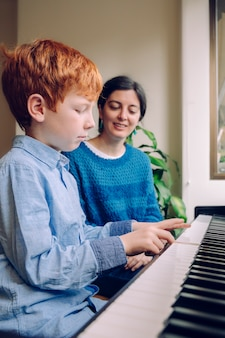음악적 미덕과 예술적 호기심을 가진 아이들. 교육적인 음악 활동. 집에서 피아노 레슨을 어린 소년을 가르치는 피아노 교사 여자. 실내에서 함께 시간을 보내는 가족 생활.