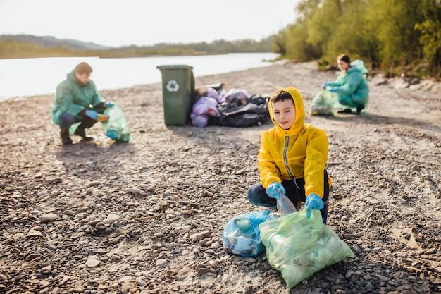 Дети с родителями убирают мусор. дети собирают мусорный мешок в лесу. загрязнение.