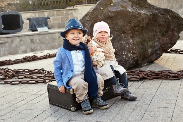Children with suitcases travel, retro autumn spring clothes