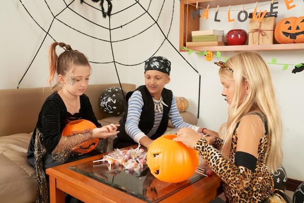 Дети со сладостями на вечеринке в честь хэллоуина