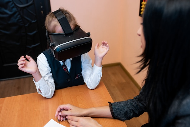 仮想現実の眼鏡をかけた子供たちは学校のオフィスにいます