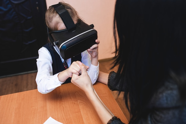 Children with virtual reality glasses are in the school office. modern teaching methods